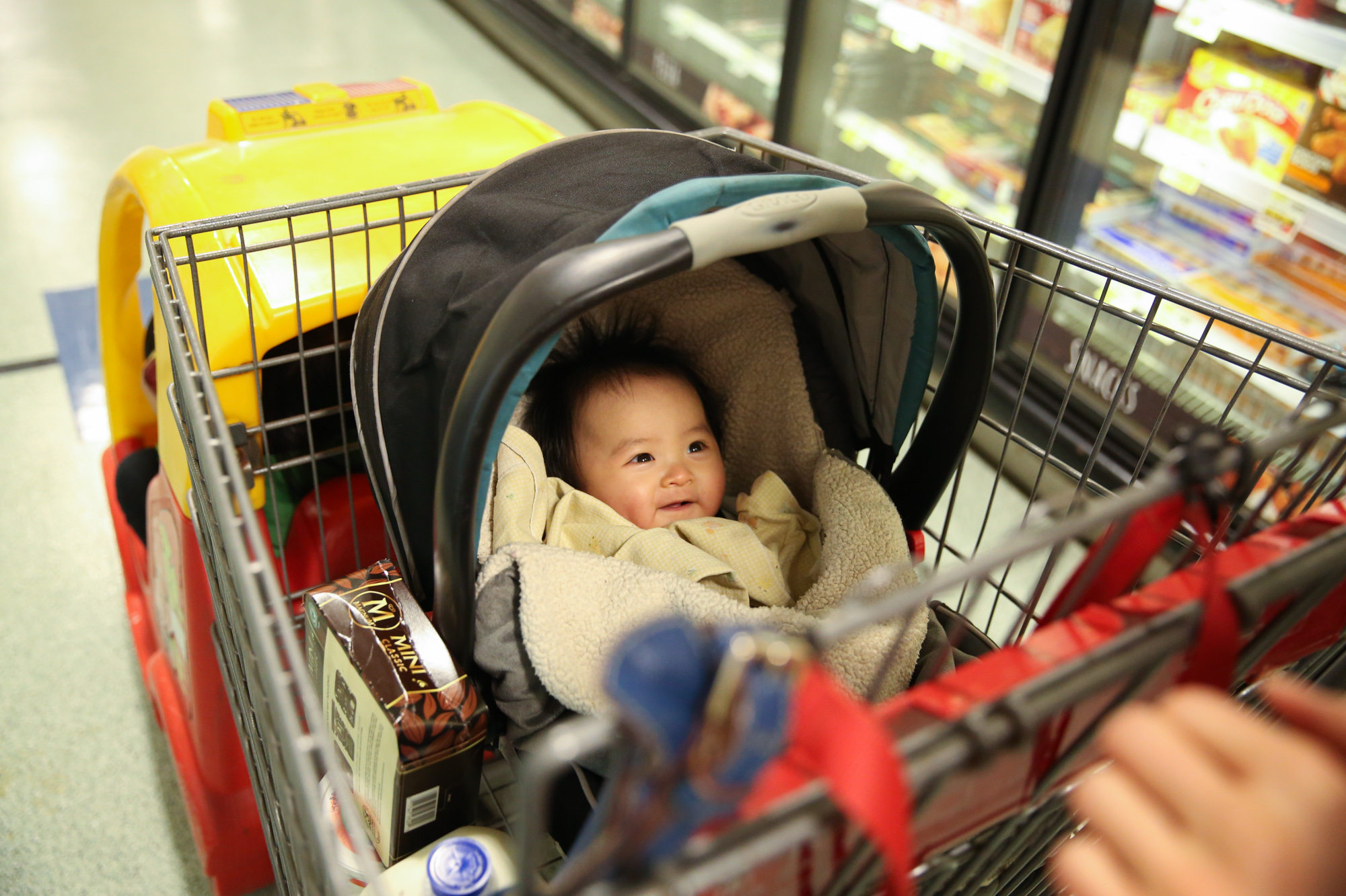 Baby smiles and looks up from bucket carseat placed inside a shopping cart with red and yellow car in front. Walking down frozen aisle in grocery store