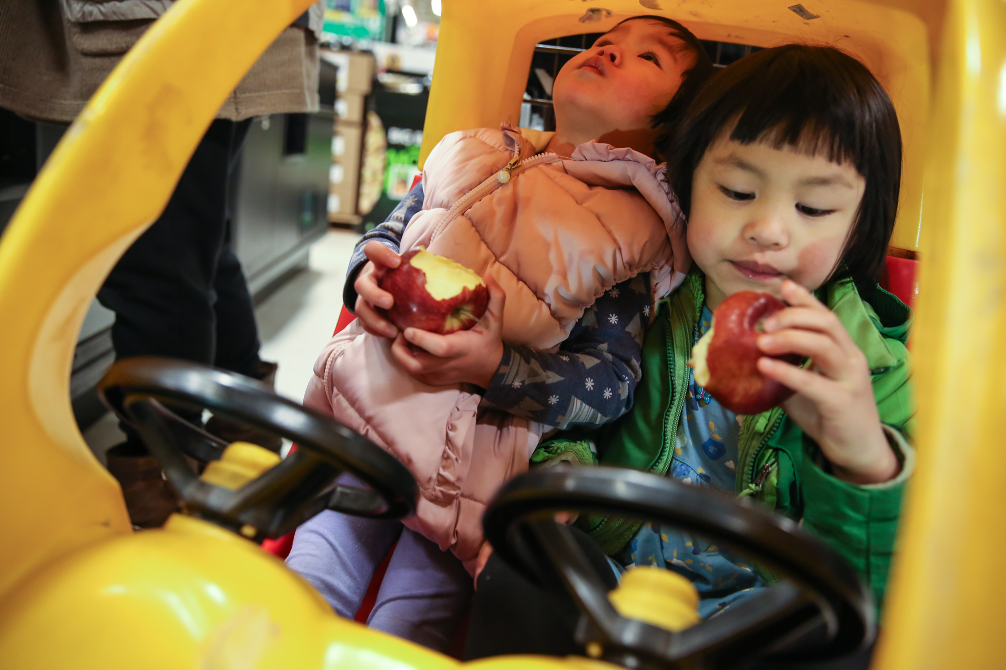 Two girls sitting in yellow toy car with steering wheels while eating red apples