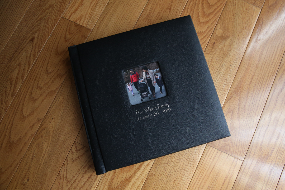 Black leather photo album with image of family, on a wood floor