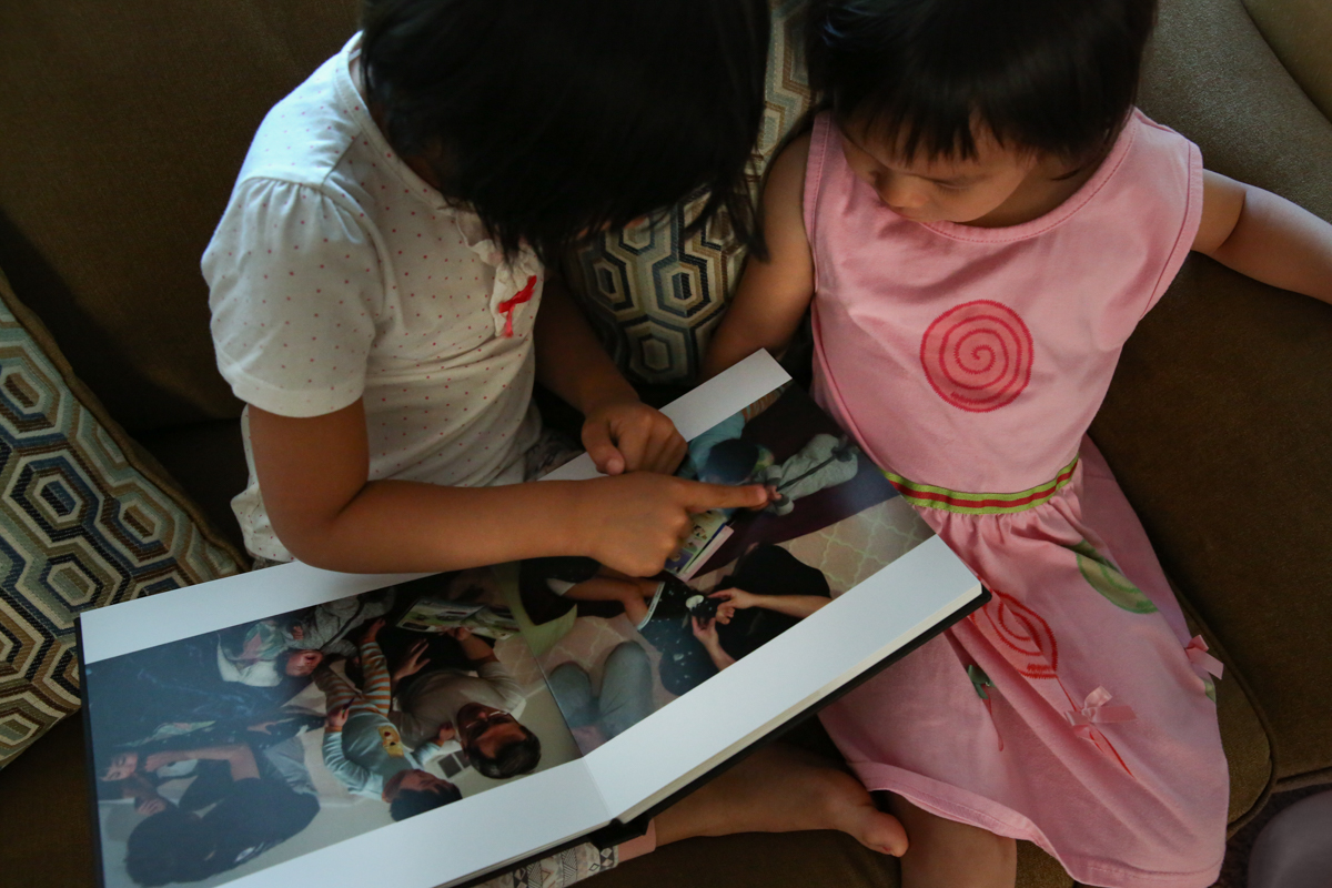 2 girls sitting on a couch looking and pointing at photo album. One girl is in a white and red polka dot shirt, the other girl is in pink dress with red swirl.