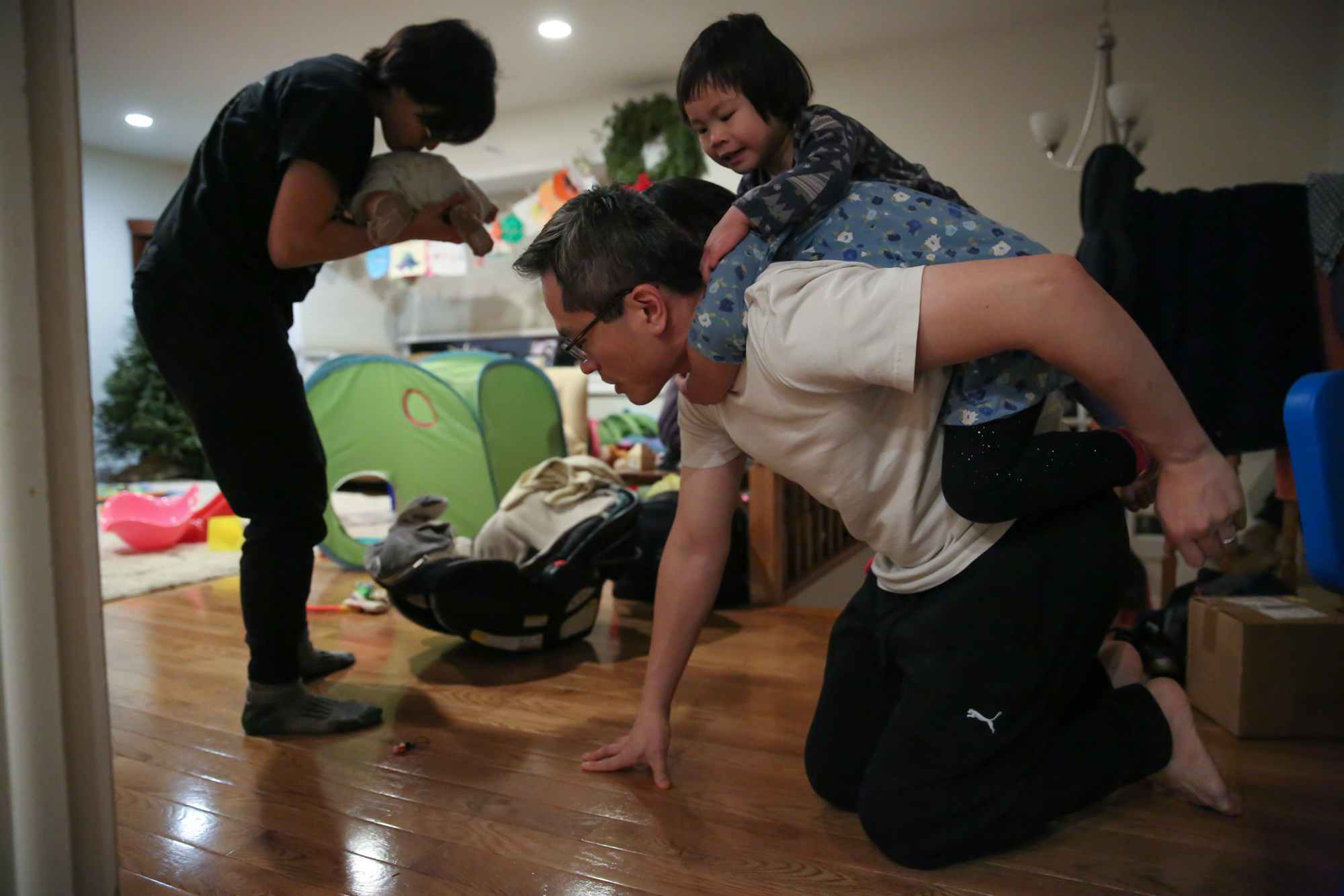Two girls climb on man's back while crouched on the floor. Woman holding baby leans over to smell baby's behind.