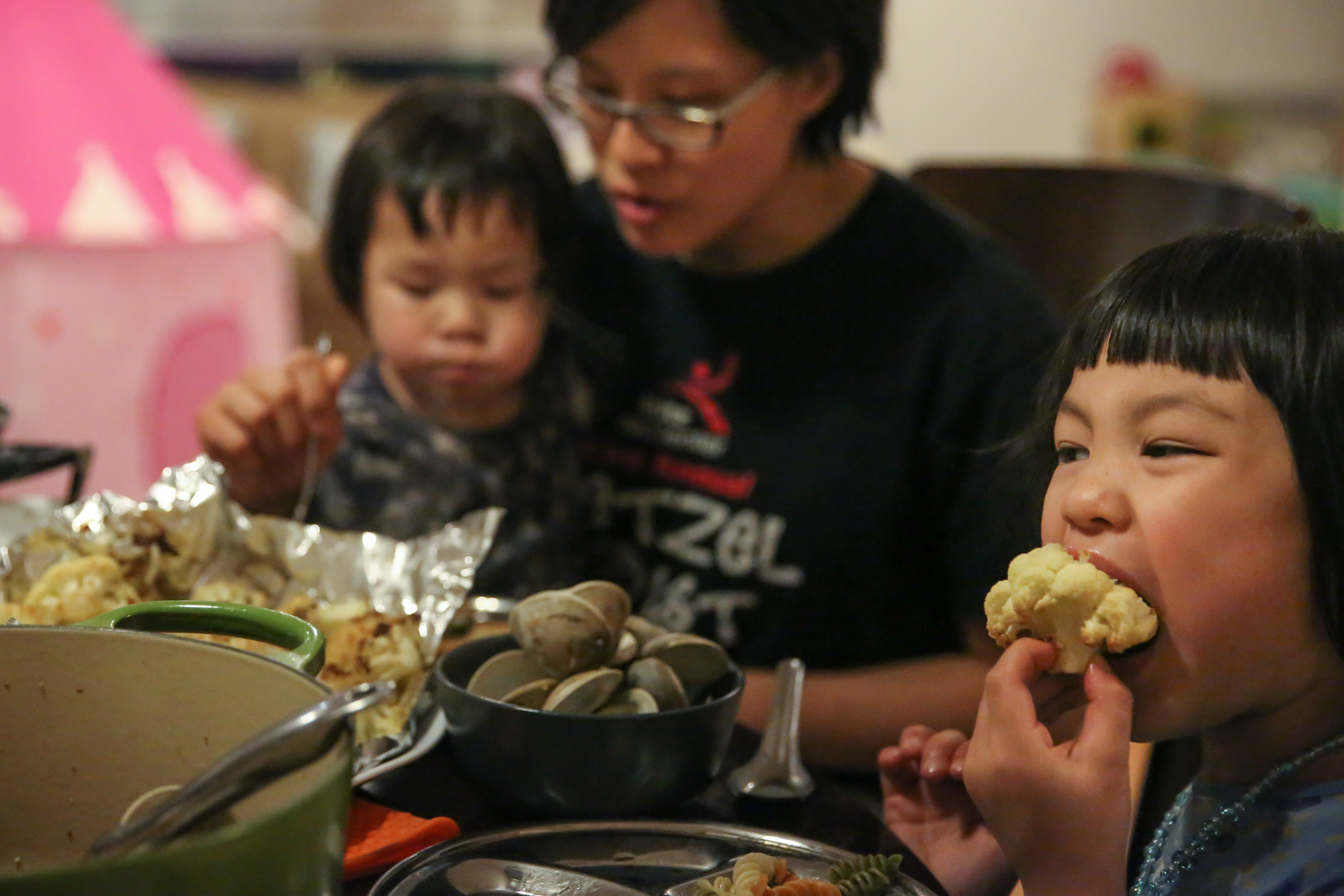 Girl takes a big bite of cauliflower with her hand. Woman sits with girl in background with a bowl of clams