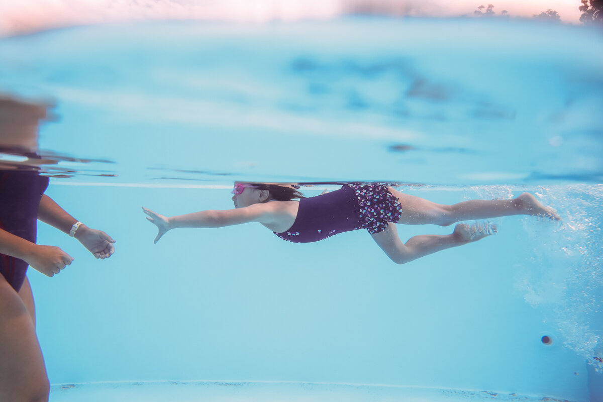Girl swims underwater reaching her hand out to swim instructor