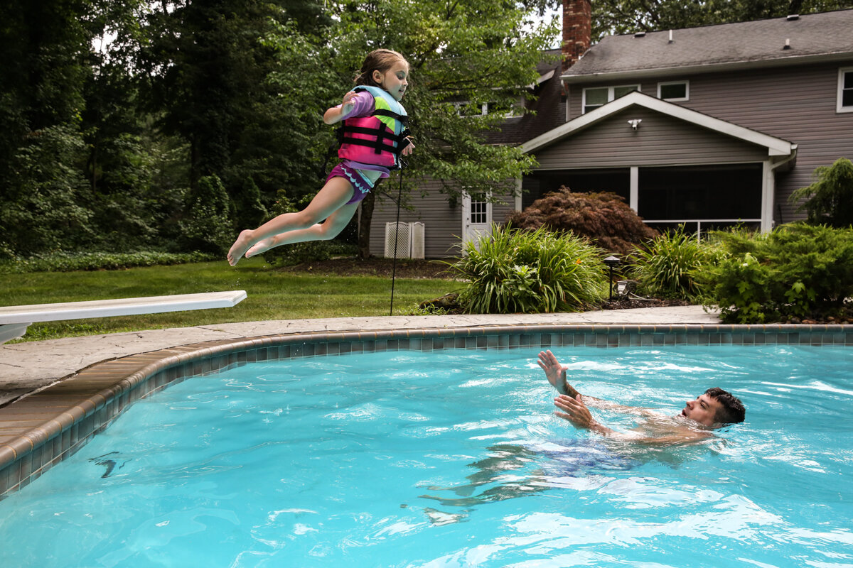 Girl wearing pink and green life vest jumps off diving board while man holds his hands and head above water in the pool to catch her