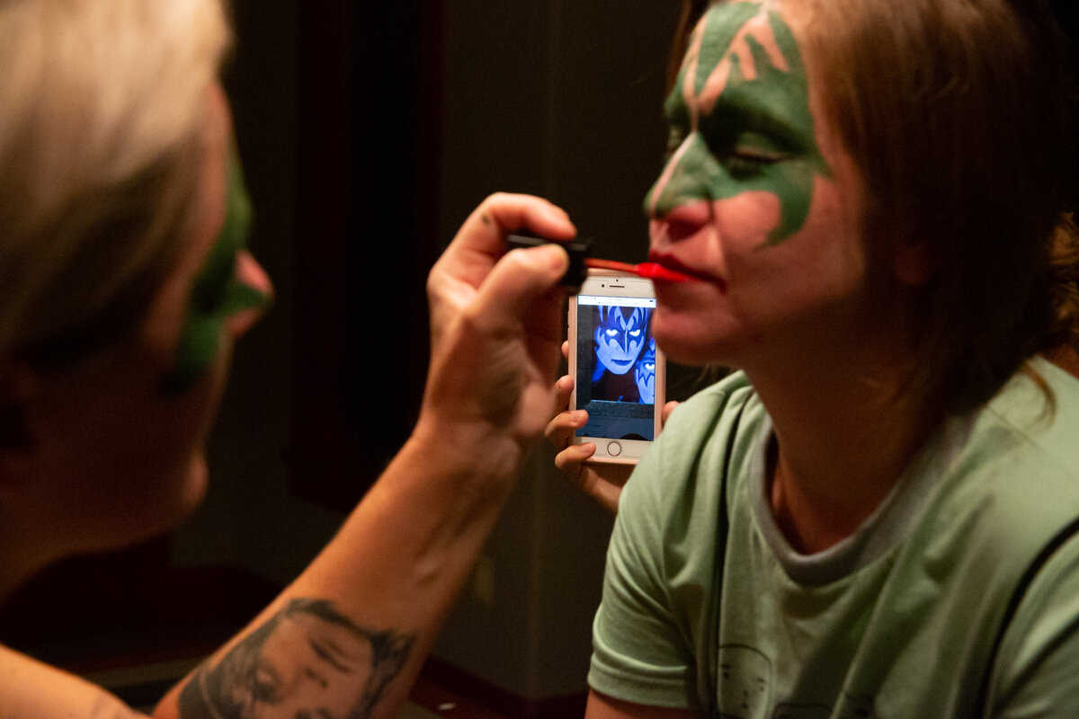 Tattooed arm applies lip color and face paint onto another woman's face. A photo of KISS is on a phone in the background
