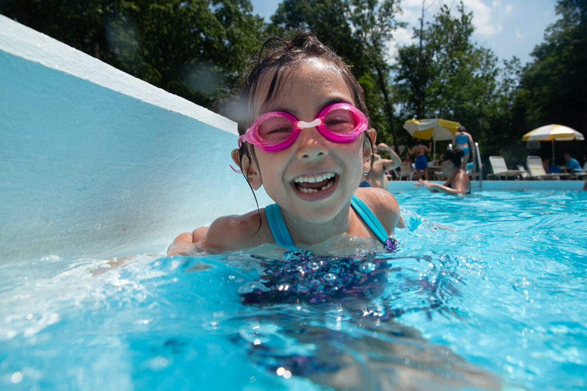 Girl with pink goggles and missing lower tooth smiles while in a swimming pool