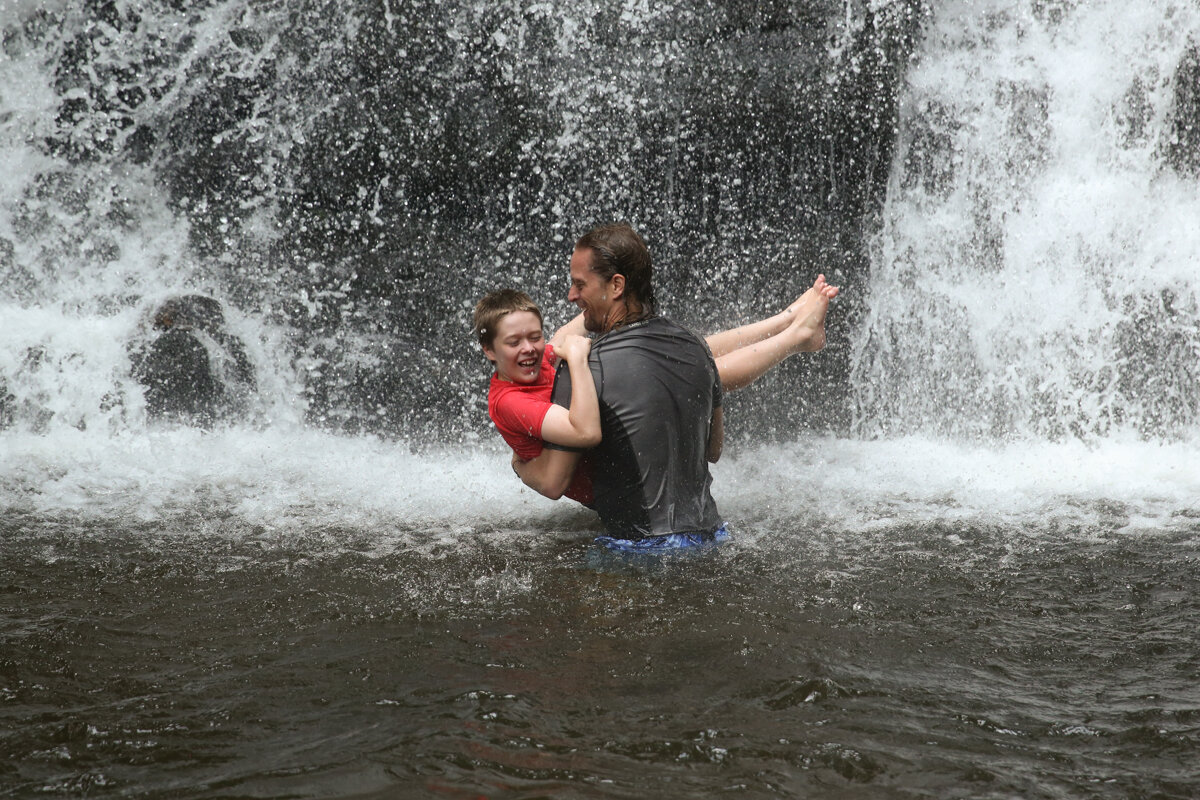 Man carries boy wearing red shirt into a waterfall