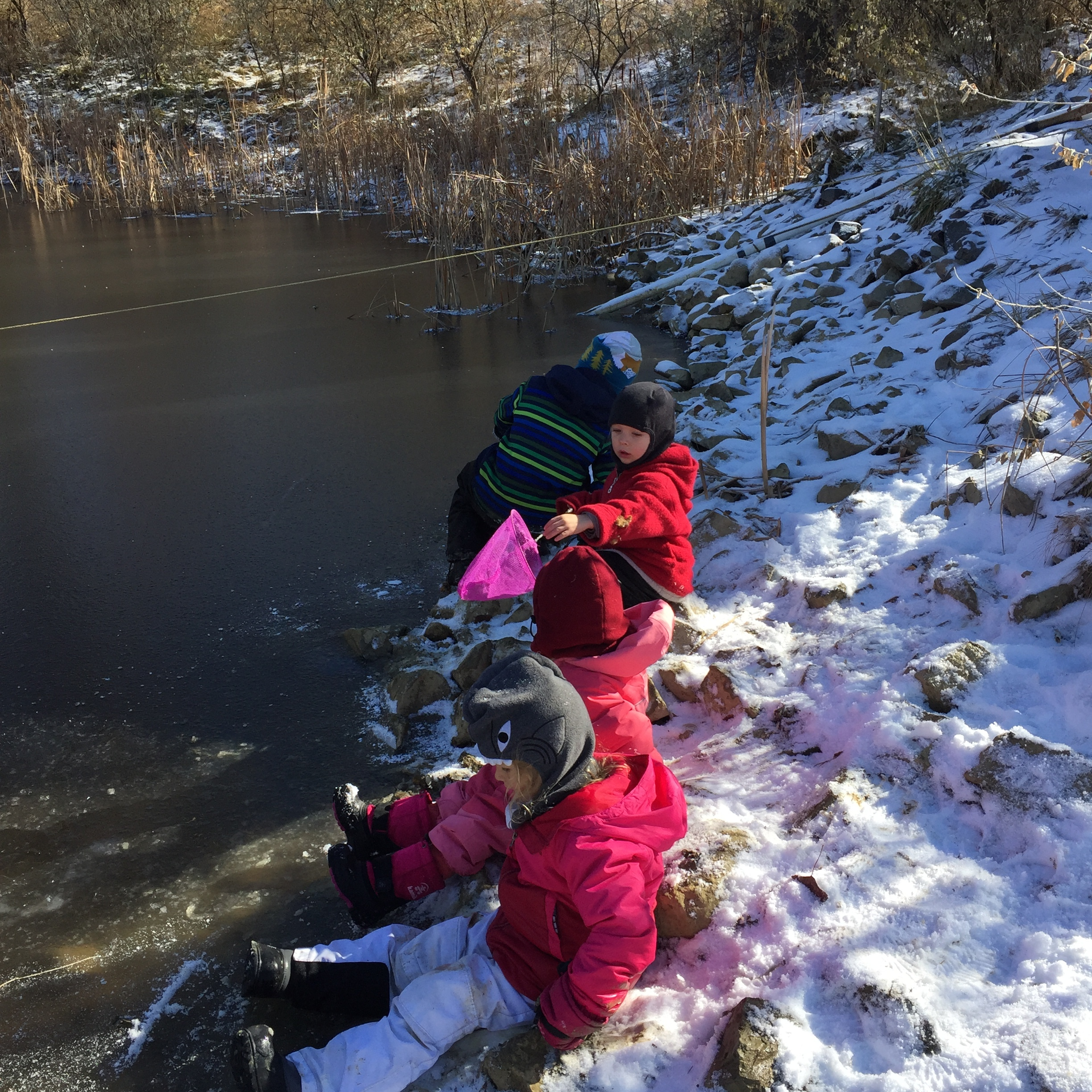 Time for some ice-safety education! The kids learned that you must never step onto an icy body of water. They sat on the shore and felt how slippery the ice was with their boots. Having the chance to experience the ice will help them understand the hazard.