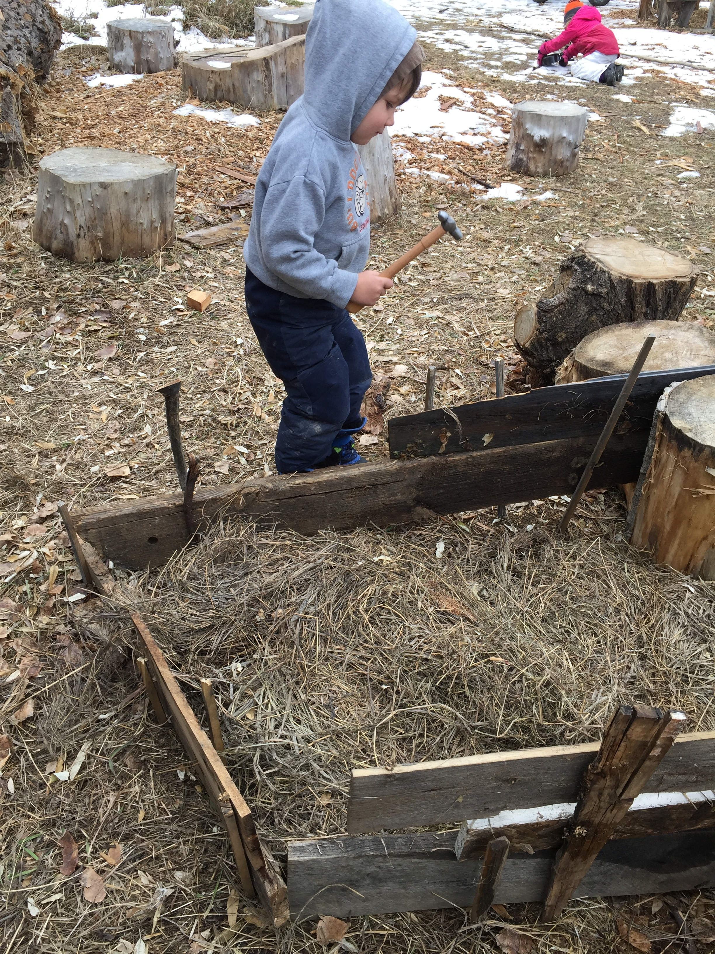 One of our builders trying out the newly discovered peg system for adding to the cabin, which now consists of two bedrooms, a living room, a woodpile and outdoor kitchen, as well as a pantry.