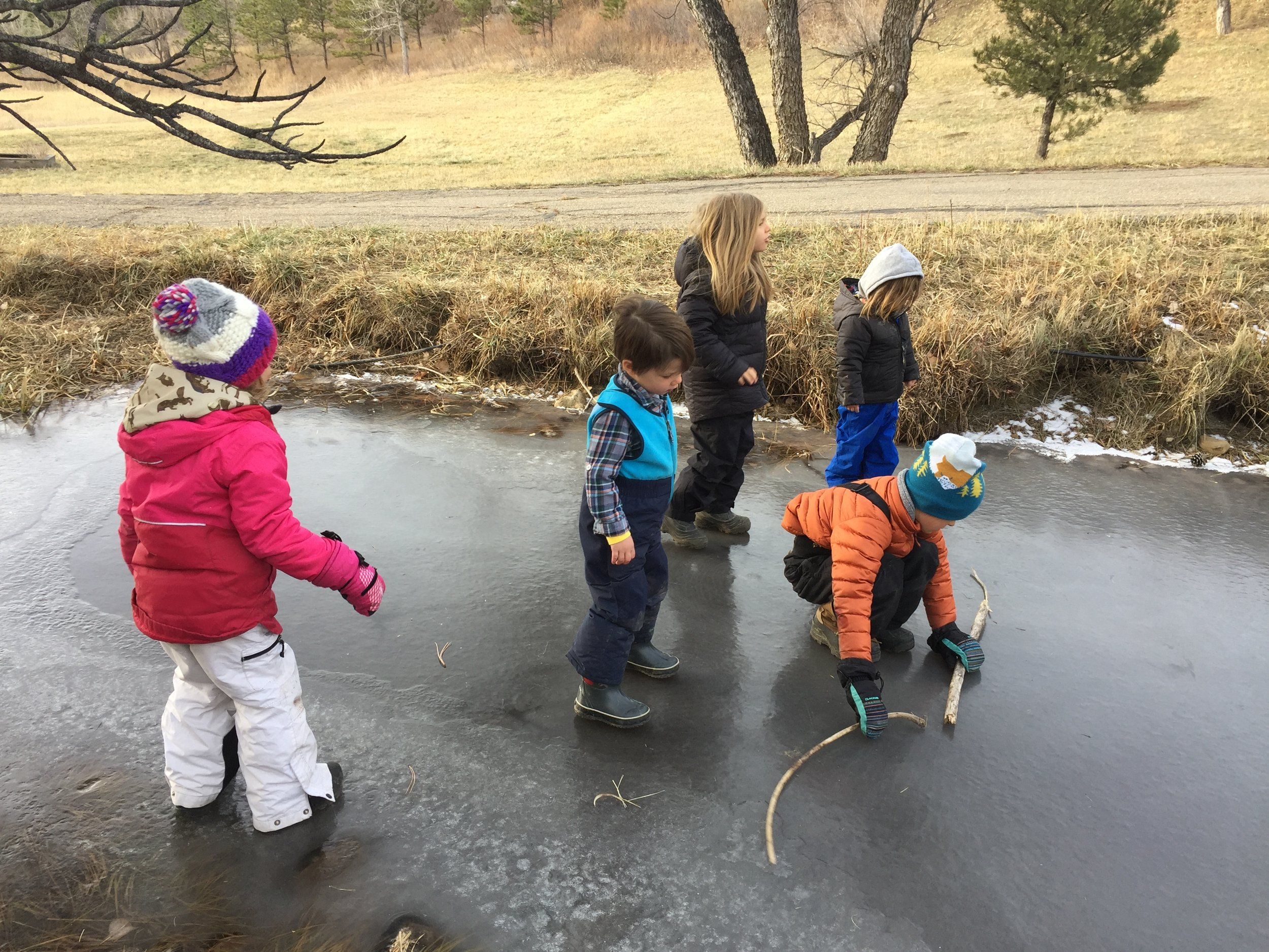 One of the older children setting a safety boundary on the shallowest end of the pond where the ice was perfect for sliding and crayfish-viewing.