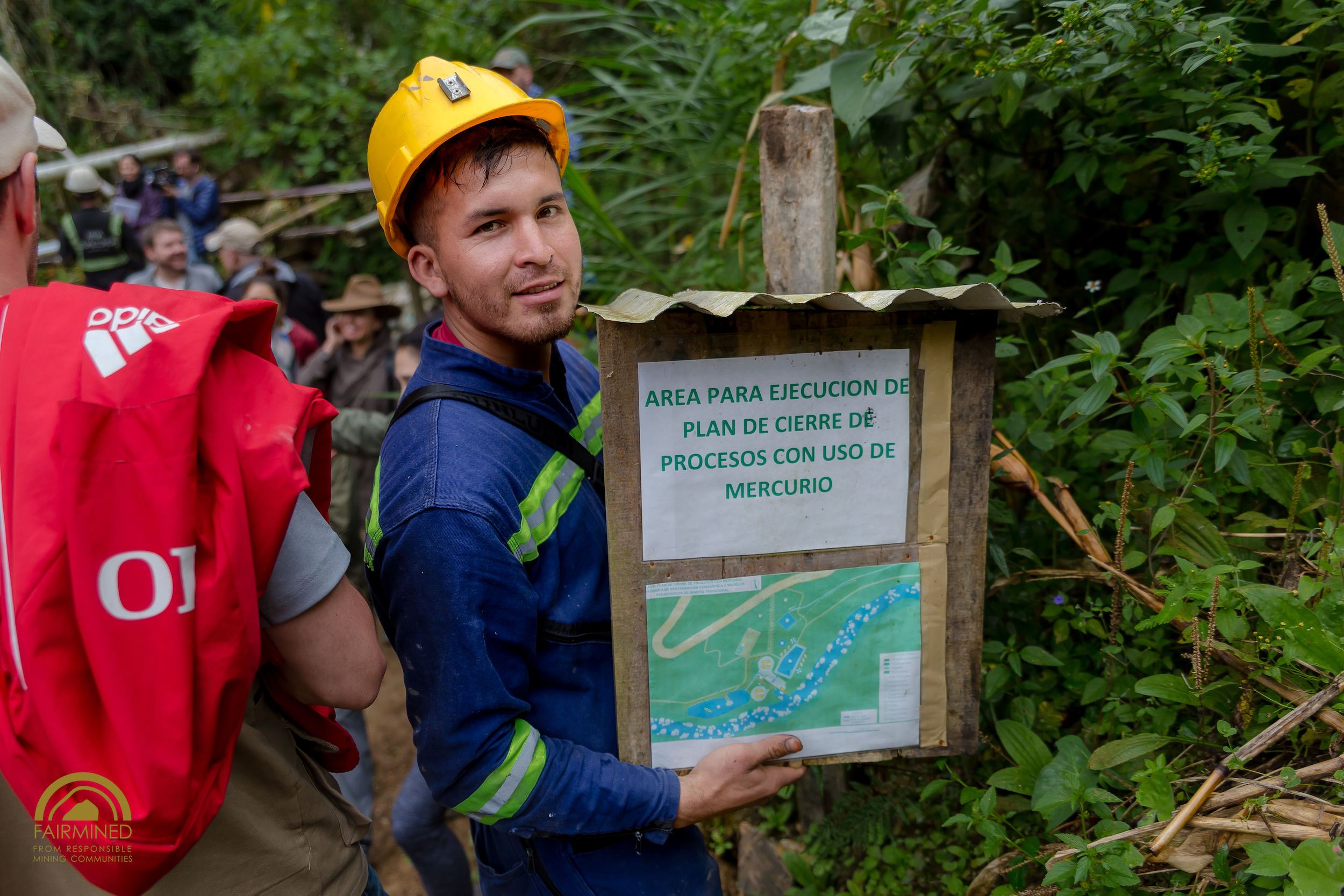 alexandre, a Miner from GUalCONDA, shows a sign Highlighting the plan for how the mercury contaminated site will look after restoration. IMAGE: Fairmined