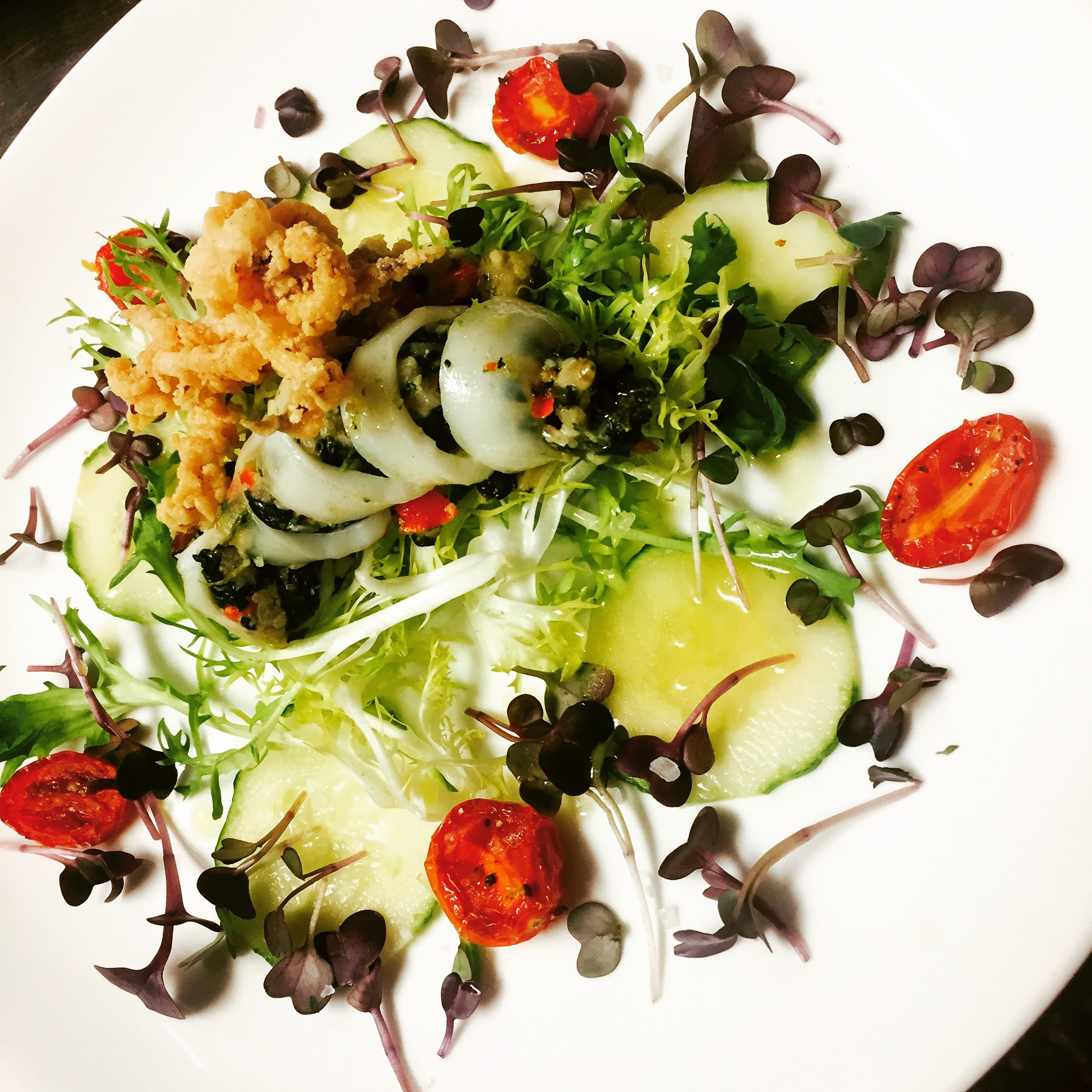 Stuffed and fried calamari on a bed of salad with tomatoes and cucumbers.