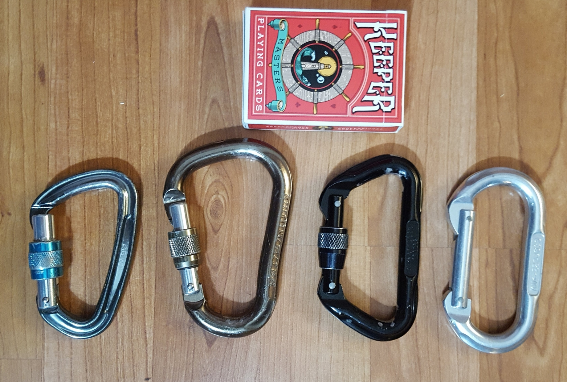 "Different sizes/shapes of carabiners (pack of cards for scale). From the left: 1) ""Big Wall Traverse"" brand small pear shaped screw gate carabiner. Not recommended for most applications as the smaller size and steeper slope makes your rope more likely to jam. 2) ""Black Diamond Rocklock"" pear shaped screw gate carabiner. Note the gentler slope than 1. This is the shape of carabiner I prefer for most applications. 3) D-shaped screw gate carabiner. Good for hanging your ring/spinner, not for much else. 4) Oval shaped carabiner without locking gate. Because it does not lock, this one is useful only for non-critical lines (although it is a climbing rated carabiner). Oval shaped carabiners (with locking gates!) are OK for hanging your points (but not as good as D-shaped carabiners) and OK for running pulleys with your rope (but not as good as pear-shaped carabiners)."