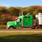 Photo:  Large green tractor trailer truck at speed in a blur.