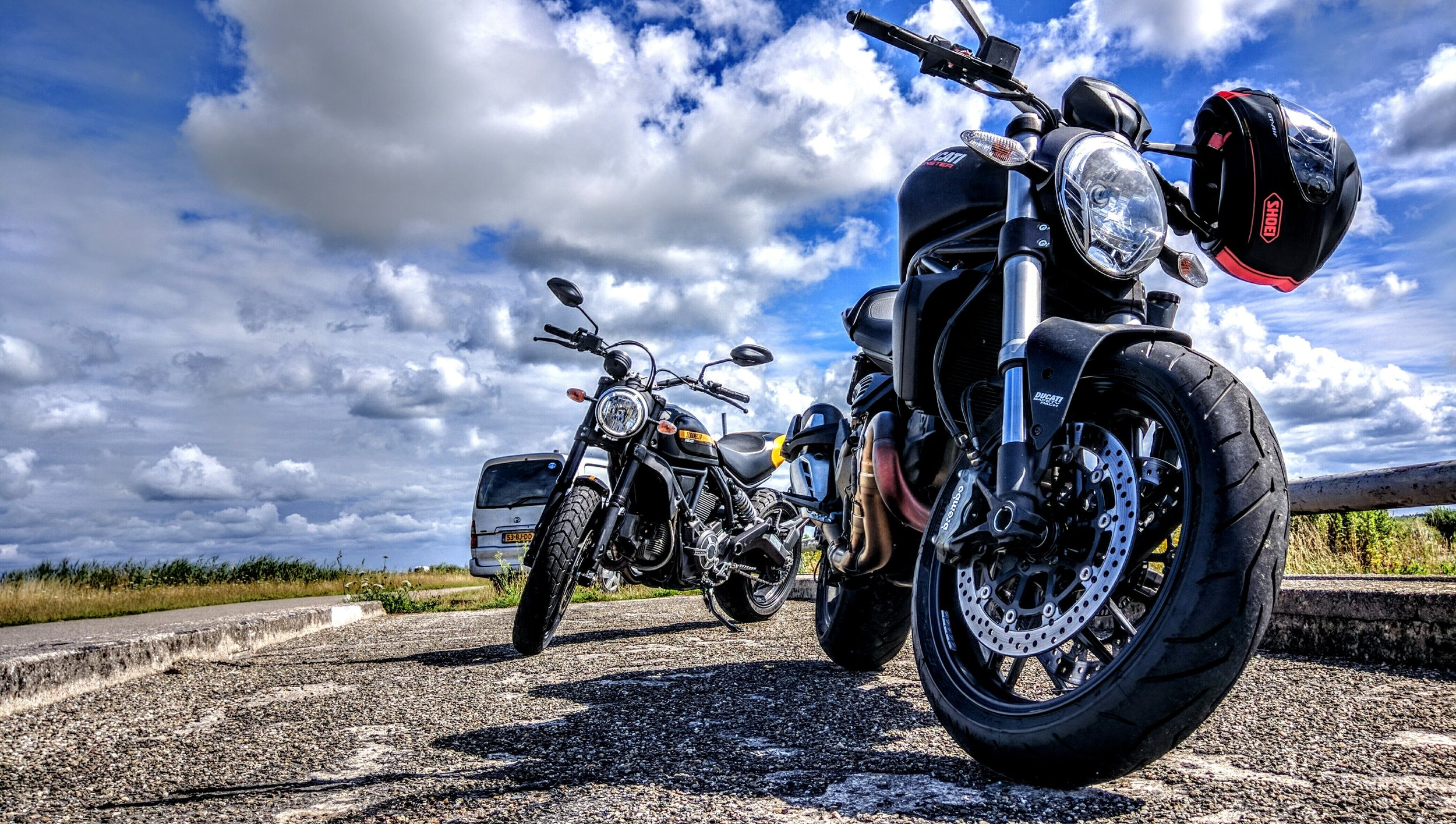 Photograph: Two motorcycles parked against a beautiful blue sky with dramatic clouds.