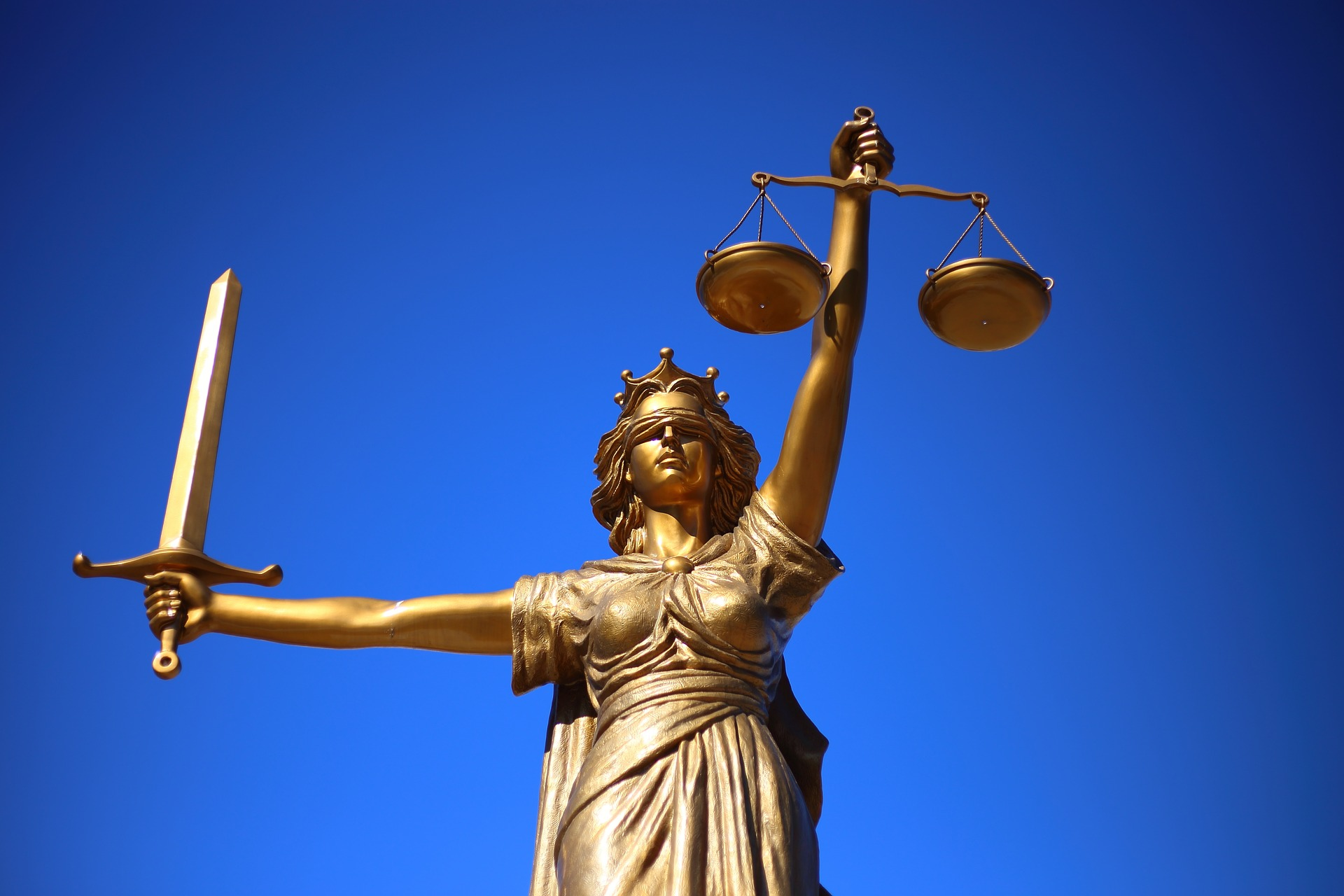 Photograph: Gold statute of Blind Lady Justice holding a sword and scales.