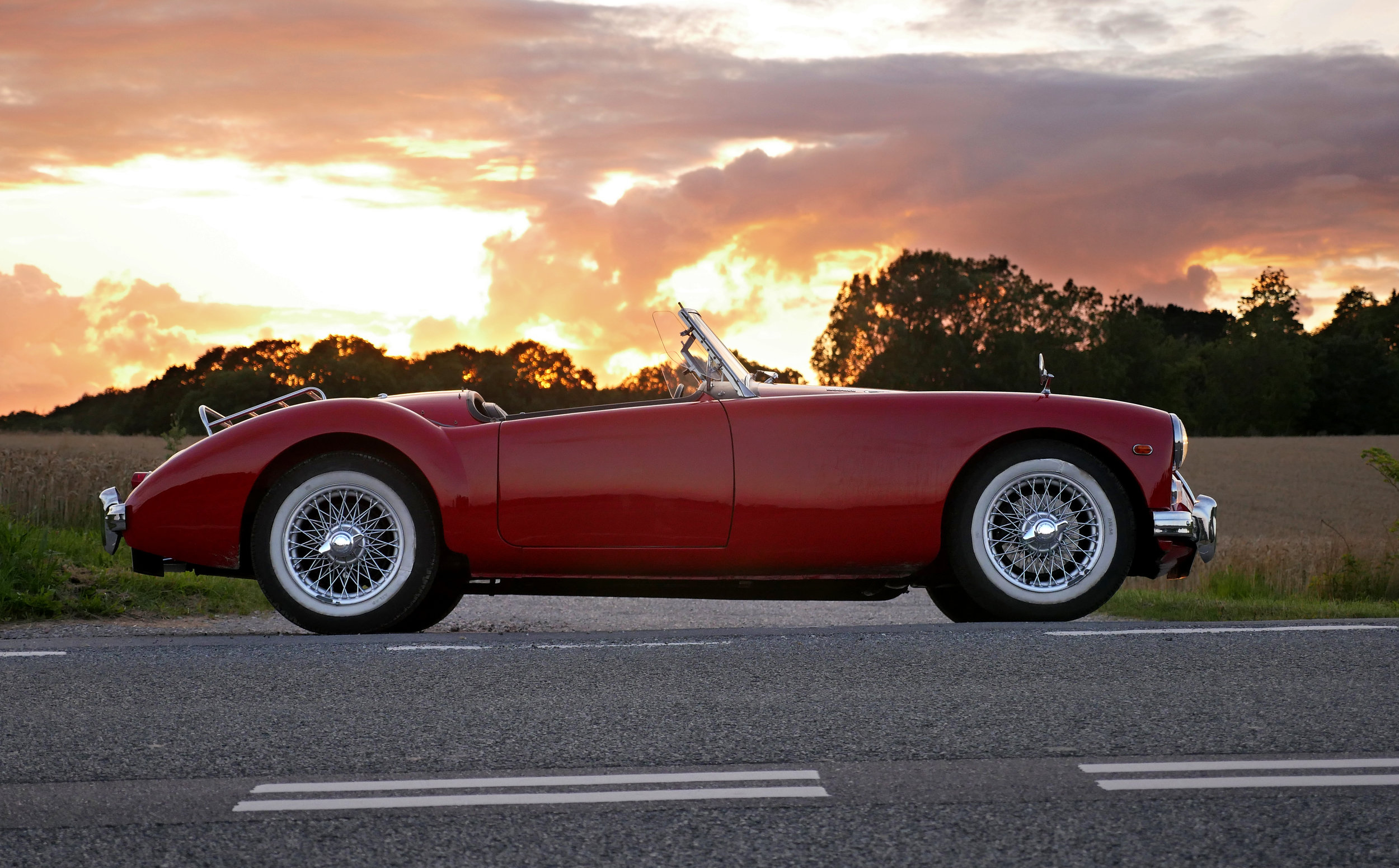 Photograph: Beautiful restored red MGA sports car against a dramatic orange sunset.