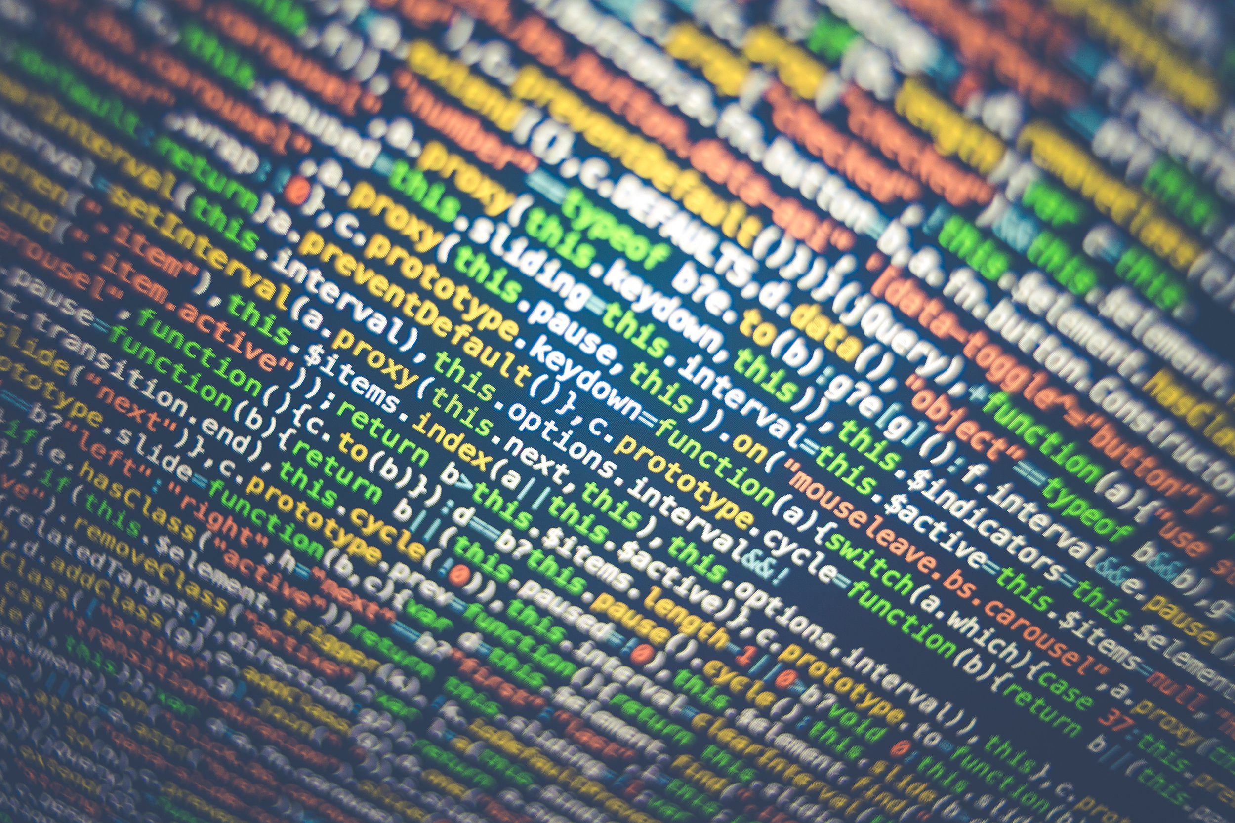 Photograph: Close up photograph of computer screen with lines of colorful code.