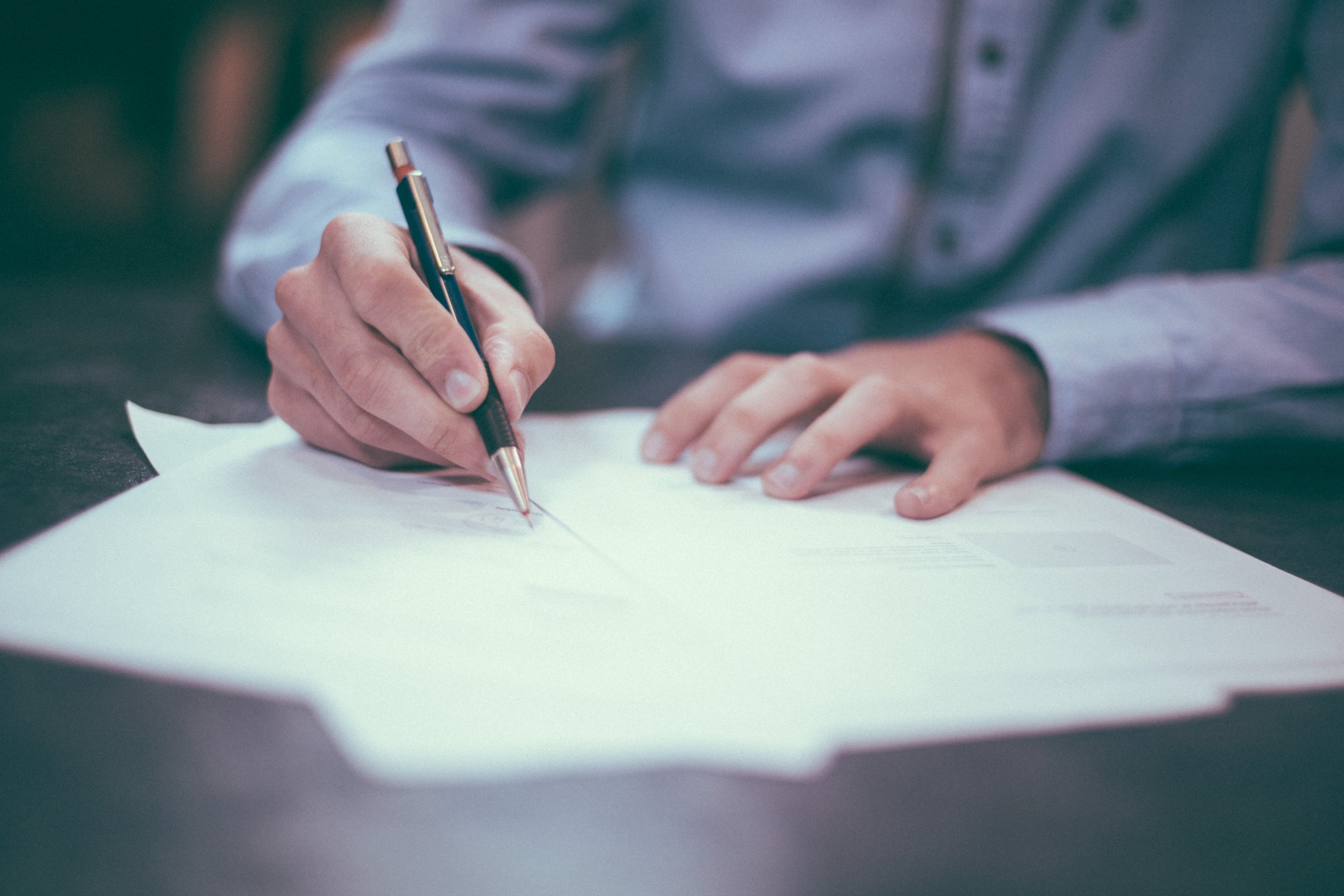 Photograph: Close-up of man's hand holding a pen while signing a document.
