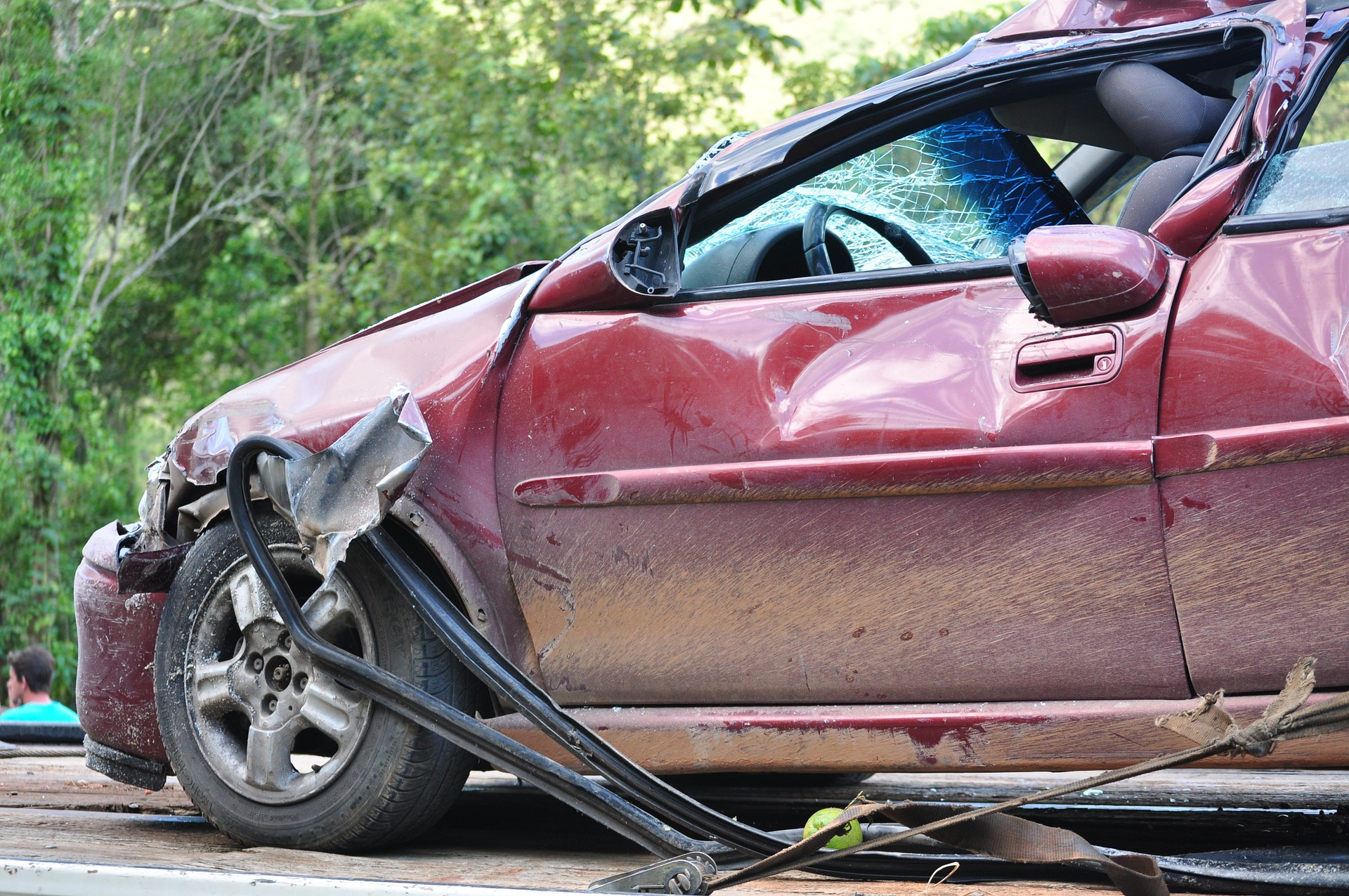 Photograph: Red car on flatbed with smashed front end from a collision.