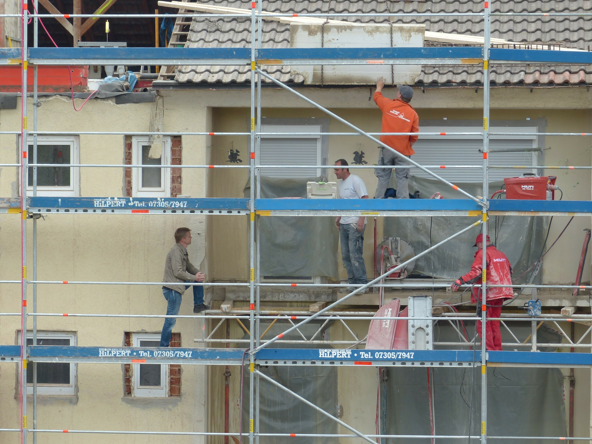 Photograph: Workings standing and climbing on scaffolding at a worksite.