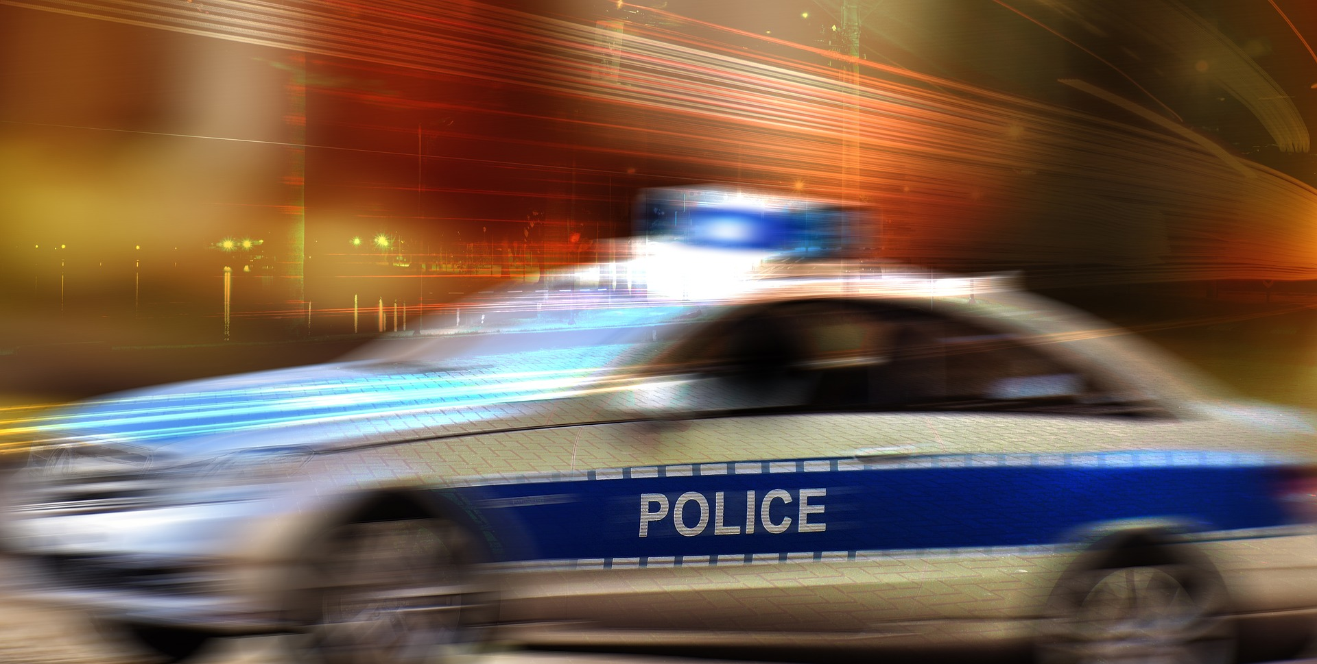 Photograph:  Speeding police car in a blur with its emergency lights on.