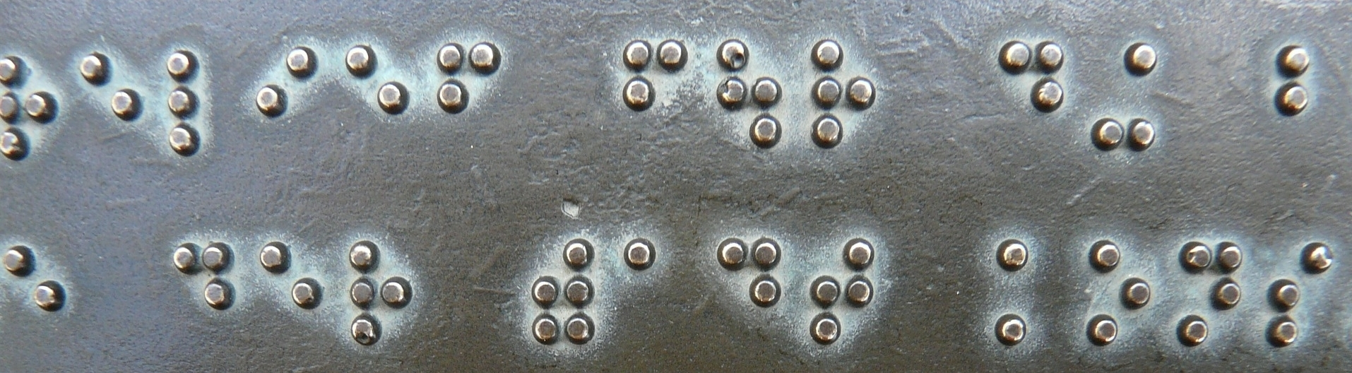 Photograph: Picture of well-used Braille letters embossed in a metal sign.