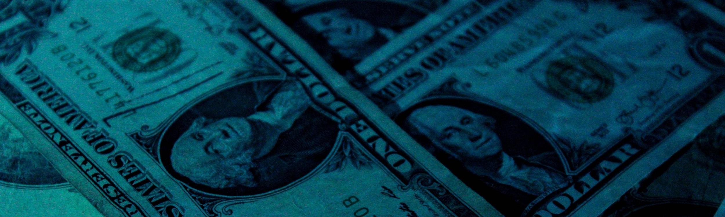 Photograph; dollar bills lying on a flat surface.