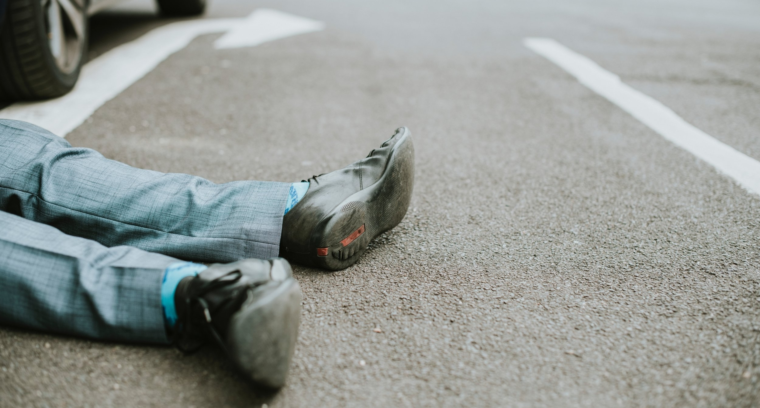 Photograph: image of feet from an unconscious person laying in front of a car.