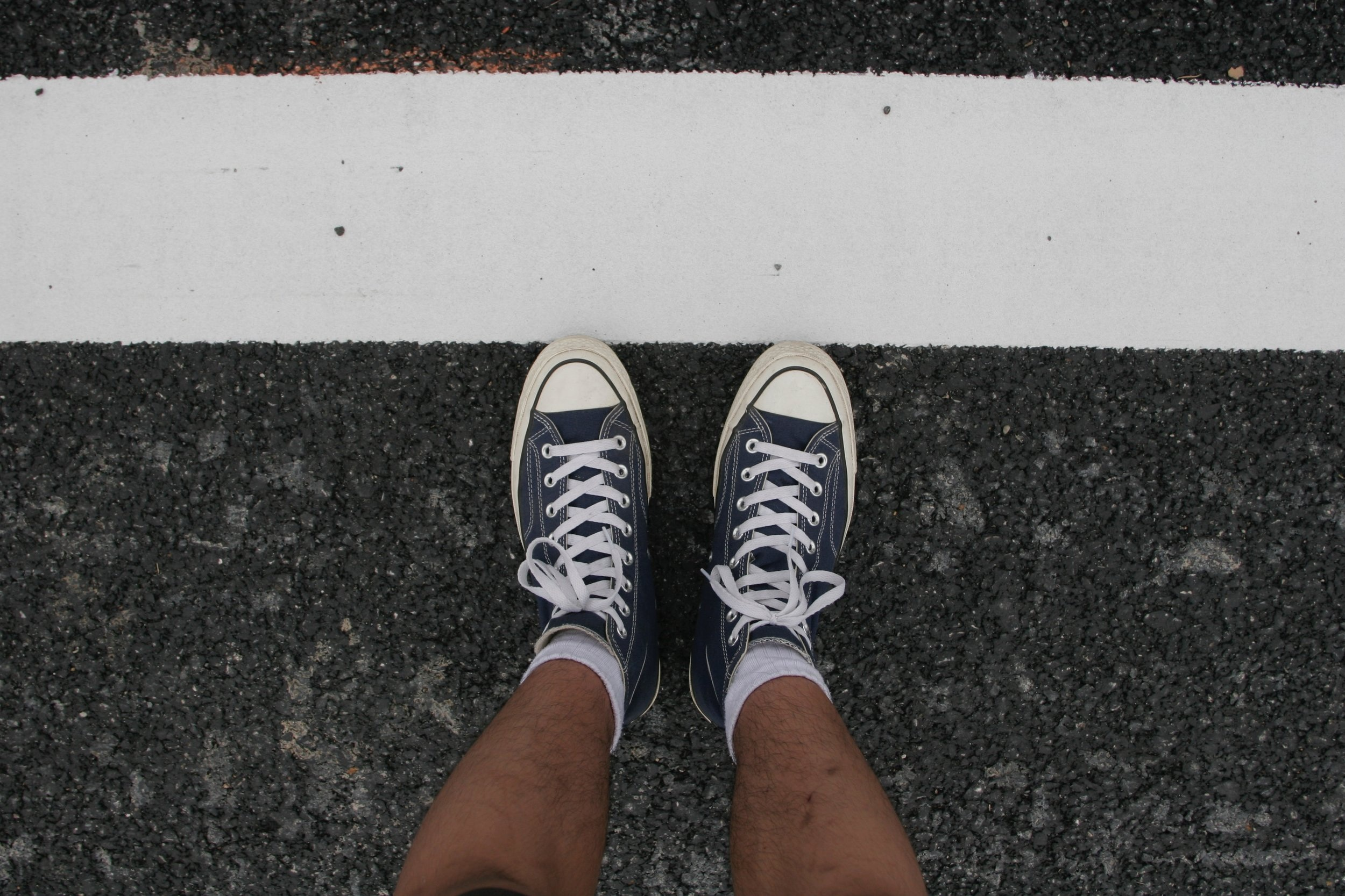 Photograph: Sneakered feet with toes touching a white painted borderline on the street.