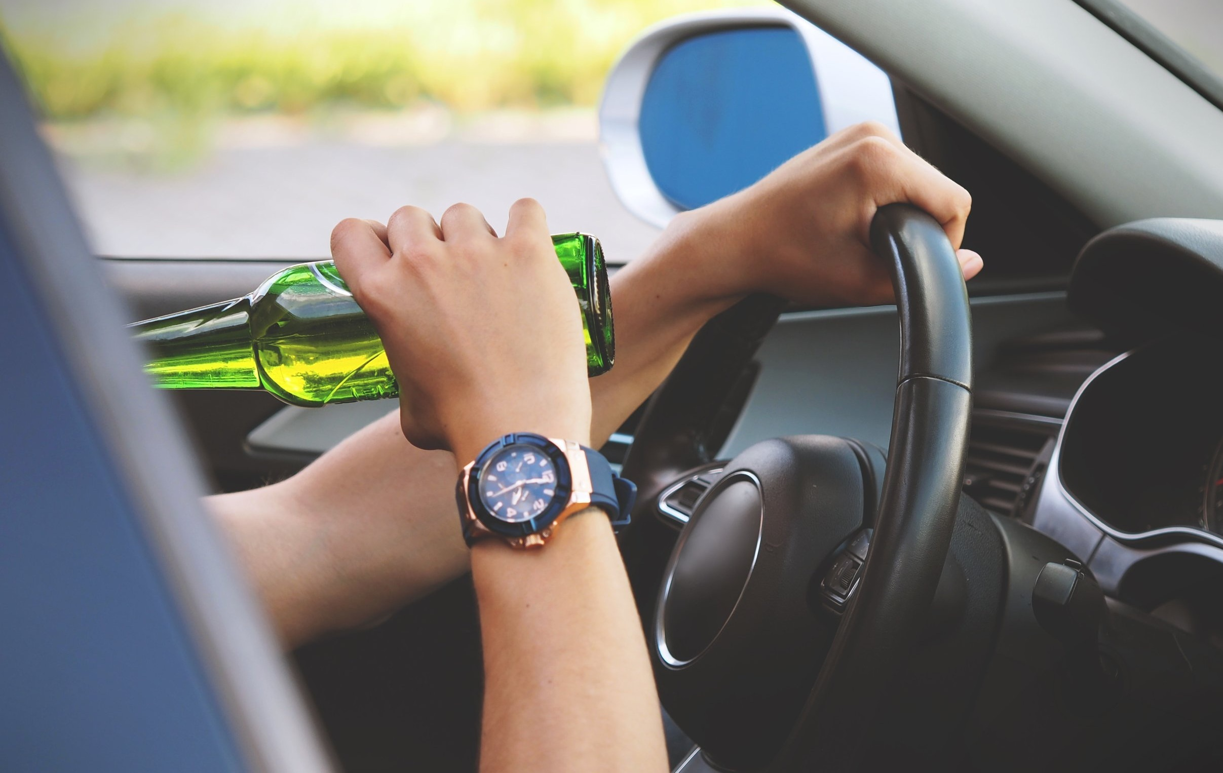 Photograph: Driver behind automobile steering wheel drinking a bottle of beer.