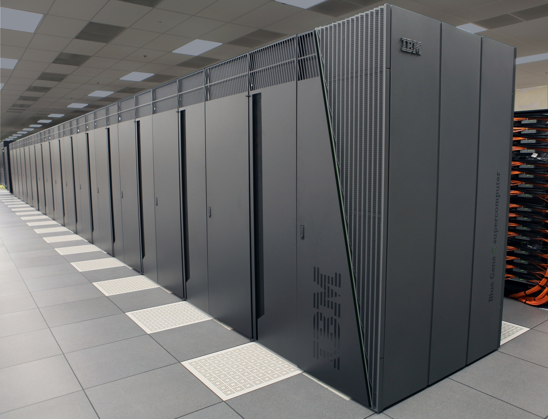 Photo: Mainframe computers lined up side-by-side in a long row in a high-tech storage facility.