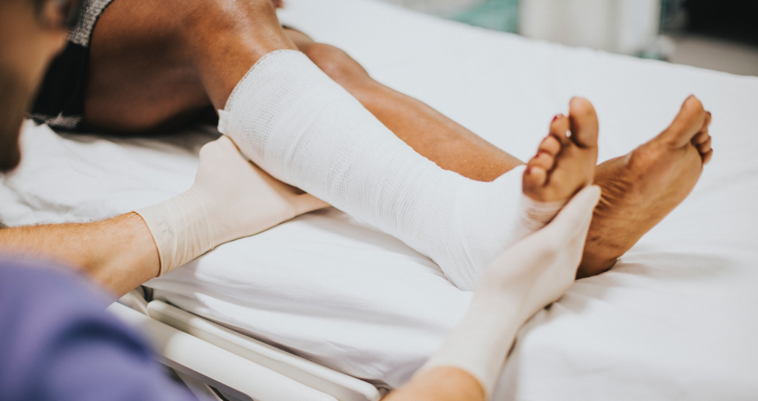 Medical provider assisting person on a hospital bed with a cast on their right leg.