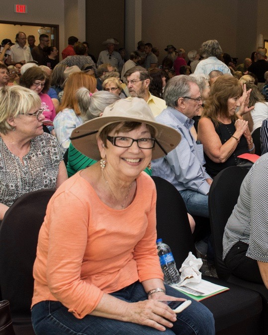 Linda Harris is more often behind a camera but provides a happy subject in the front row at a huge town hall meeting in Las Cruces. The group kept up the pressured on Steve Pearce (R-NM) to hold a public meeting in town, even following him to town hall meetings in other towns. -