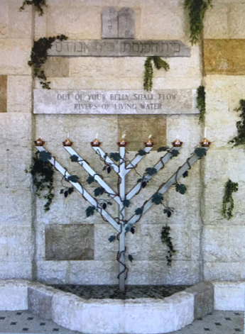 MENORAH - FOUNTAIN JERUSALEM STONE     As you enter the lobby of the Synagogue, you will notice a Jerusalem Stone wall supporting a Menorah rising from a fountains, designed by local Messianic Pastor, Burt Yellin.