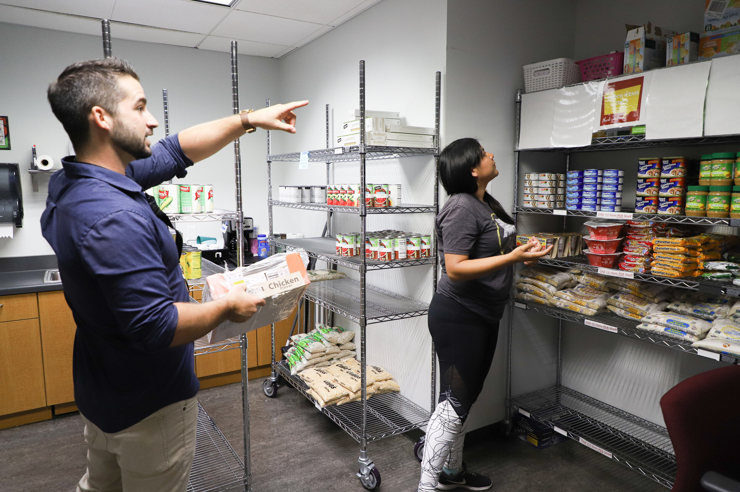 Nicholas Slobin/ Courier James Bull, manager of the Lancer Pantry, and English major Sarahy Medina, 23, from Los Angeles, organize food items in the Lancer Pantry at PCC on Friday, September 13, 2019.