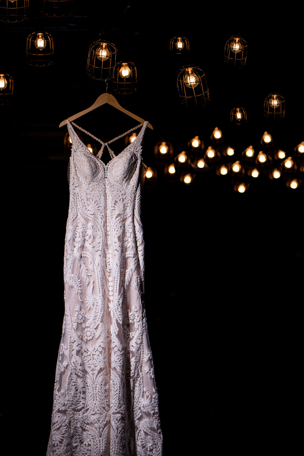 Detail shot of a hanging wedding dress in a brewery,part of a Boho Brewery WeddingStyled Shoot at Triple C Barrel Room in Charlotte NC. Wedding dress is from Paige and Elliot.