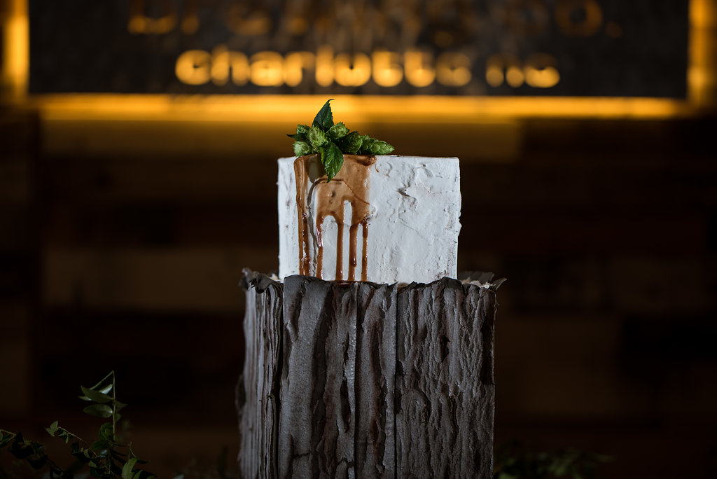 Detail shot of a beer themed Wedding Cake that looks like wood, part of a Boho Brewery Wedding Styled Shoot at Triple C Barrel Room in Charlotte NC. This cake has hops and beer running down the side!Wedding cake by The Wow Factor Cakes.