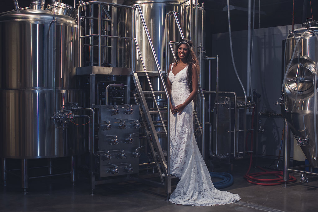 Bridal Portrait of a bride in a brew room,part of a Boho Brewery Wedding Styled Shoot at Triple C Barrel Room in Charlotte NC. Dress and accessories by Paige and Elliot.