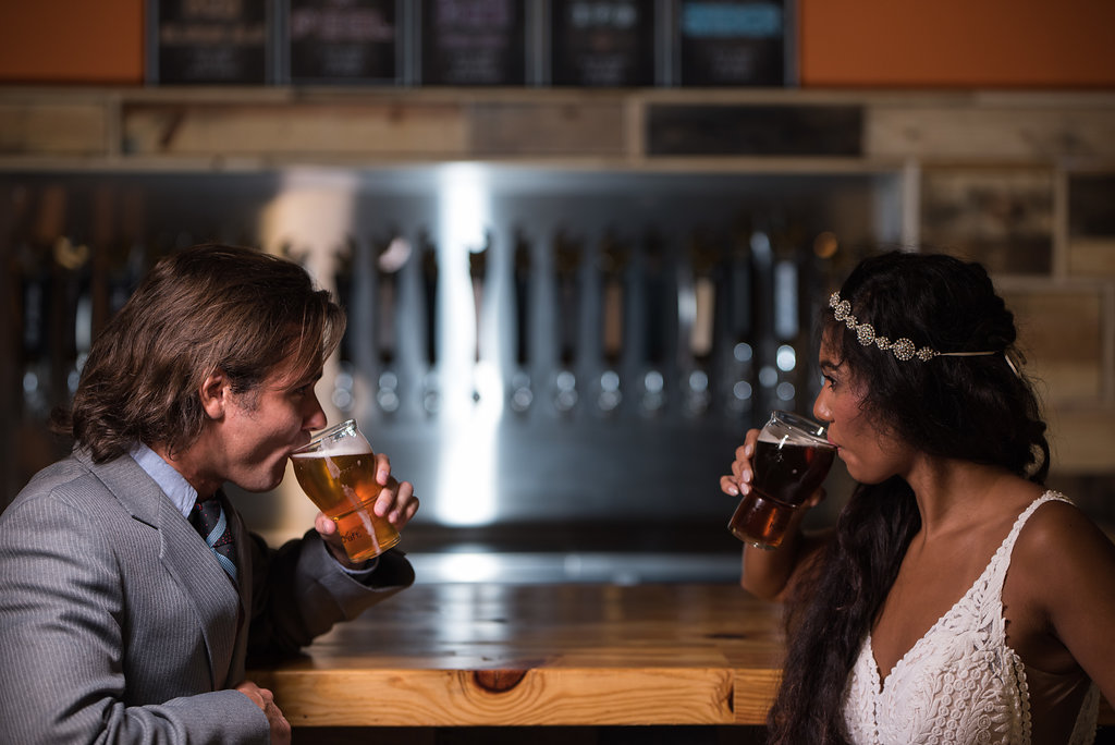 Bride and groom drinking beer,part of a Boho Brewery Wedding Styled Shoot at Triple C Barrel Room in Charlotte NC. Dress and Accessories by Paige and Elliot.