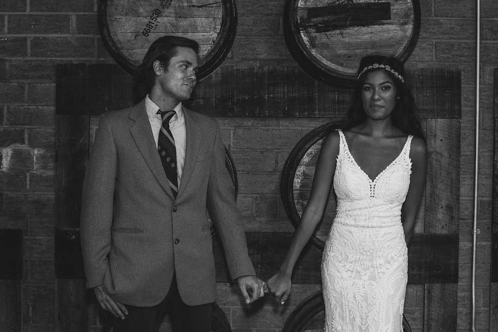 Bride and Groom together with barrels,part of a Boho Brewery Wedding Styled Shoot at Triple C Barrel Room in Charlotte NC. Dress and Accessories by Paige and Elliot.