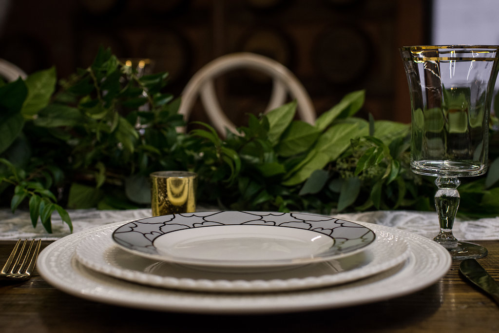 Detail shot of empty table setting with plates and goblets,part of a Boho Brewery Wedding Styled Shoot at Triple C Barrel Room in Charlotte NC. Table and setting provided by Best Impressions Caterers and Party Reflections.