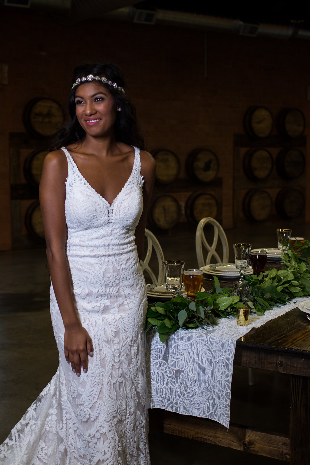 Bridal portrait at food table,part of a Boho Brewery Wedding Styled Shoot at Triple C Barrel Room in Charlotte NC. Dress and Accessories by Paige and Elliot.