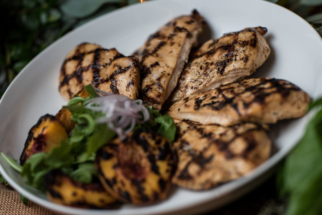 Detail shot of food, grilled chicken with grilled peaches,part of a Boho Brewery Wedding Styled Shoot at Triple C Barrel Room in Charlotte NC. Table,setting, and food provided by Best Impressions Caterers and Party Reflections.
