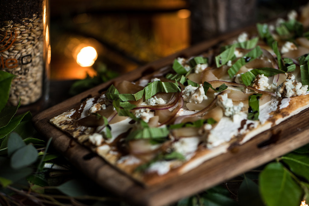 Detail shot of food, arugula and goat cheese flatbread,part of a Boho Brewery Wedding Styled Shoot at Triple C Barrel Room in Charlotte NC. Table,setting, and food provided by Best Impressions Caterers and Party Reflections.