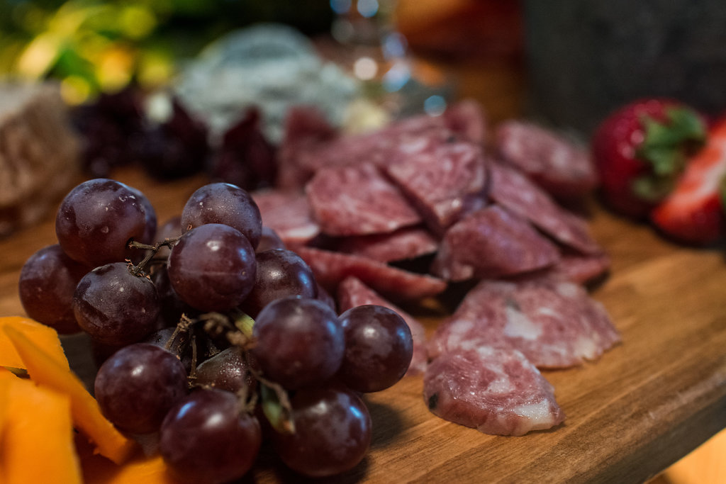 Detail shot of food, meat, cheese, and fruit spread,part of a Boho Brewery Wedding Styled Shoot at Triple C Barrel Room in Charlotte NC. Table,setting, and food provided by Best Impressions Caterers and Party Reflections.