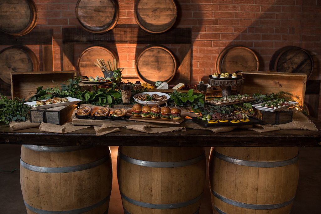 Detail shot of spread of food on barrels,part of a Boho Brewery Wedding Styled Shoot at Triple C Barrel Room in Charlotte NC. Farmhouse Table,setting, and food provided by Best Impressions Caterers and Party Reflections.