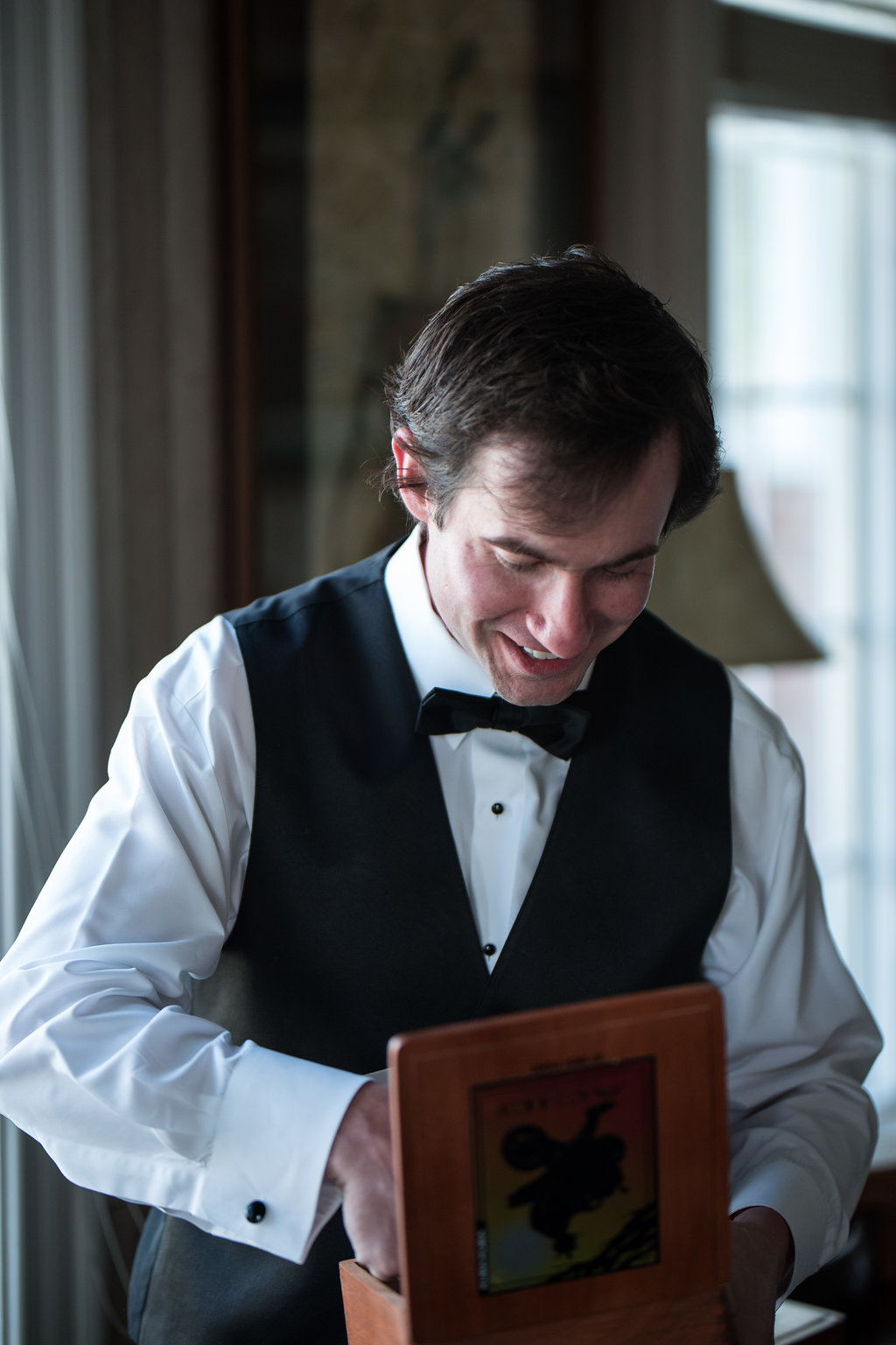 Groom opening gift in Pilot Knob Country Club. Wedding Photography by Party of Two Photography.