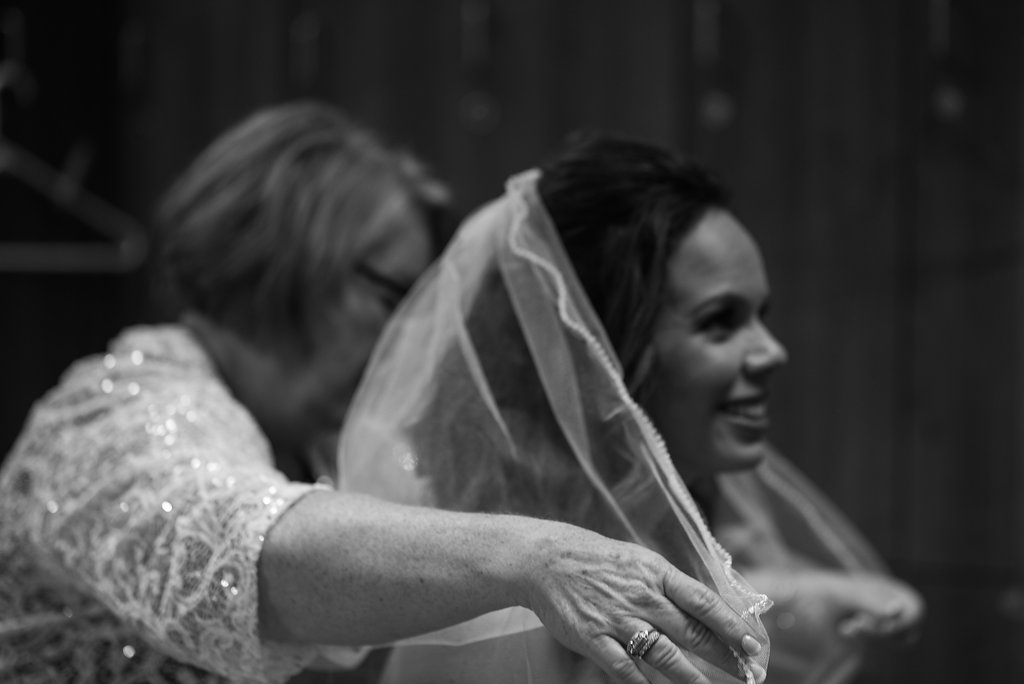 Mom helping bride with veil in Pilot Knob Country Club. Wedding Photography by Party of Two Photography.