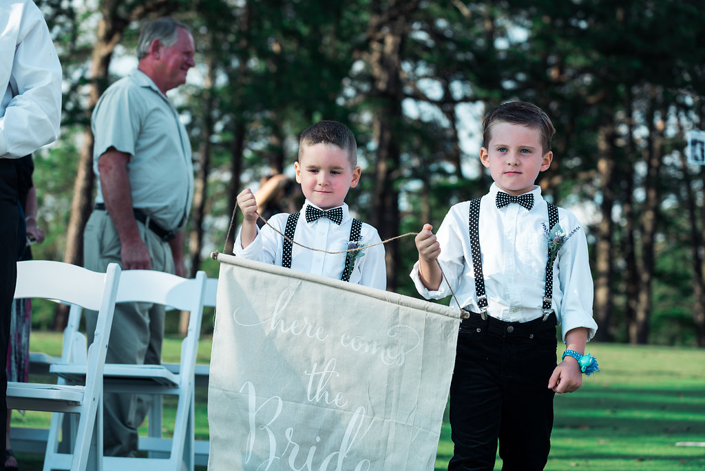 Two children bring wedding sign down aislein Pilot Knob Country Club. Wedding Photography by Party of Two Photography.